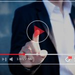Man hitting a Play button for a video